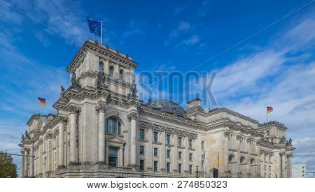 Reichstag building in Berlin, Germany. Under view of stately house, clouds travel on the sky background.