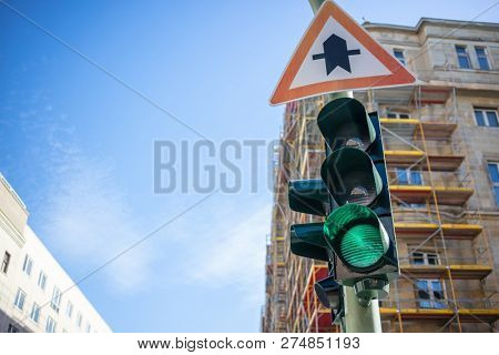 Green traffic light and traffic sign. Signal for safety route. Blue sky and buildings background. Closeup under view, space.