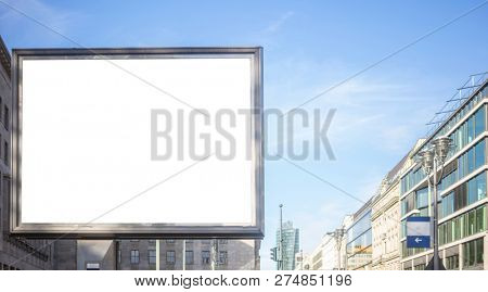 Blank billboard for public advertisement on the roadside. Space for text. Blue sky and city background.