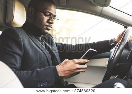 A Businessman Driving A Expensive Car Holds A Mobile Phone In His Hand. Hasty Life.