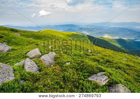 Grassy Slope With Huge Rocks. Wonderful Summer Landscape In Mountains. Winding Path Through The Dist