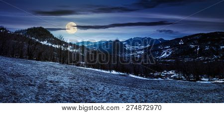 Panorama Of Mountainous Countryside In Springtime At Night In Full Moon Light. Leafless Trees And We