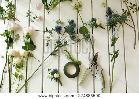 Pruner And Other Florist Tools And Cutted Fresh Flowers Lying On White Wooden Table. Event Fresh Flo