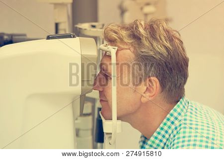Health Care, Medicine, People, Eyesight And Technology Concept - Male Checks His Vision On The Machi
