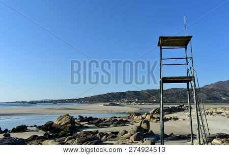 Beach With Lifeguard Tower, Lake And Rocks. Golden Sand And Blue Sea, Clear Sky. Sunset, Sunny Day,