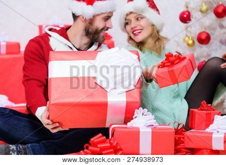 Couple In Love Enjoy Winter Holiday Celebration. Woman And Bearded Man In Love Sit Near Christmas Tr