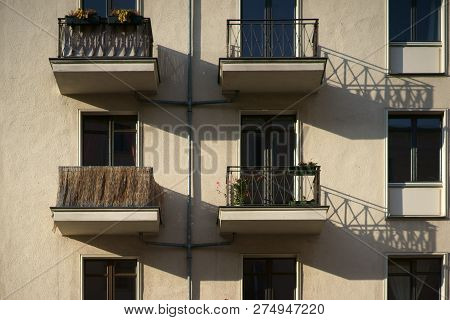 The railings of small nostalgic balconies of an apartment building cast shadows. poster