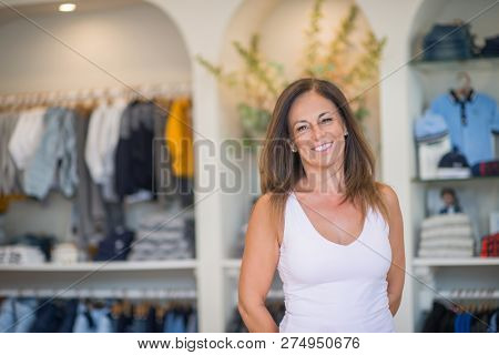 Beautiful middle age hispanic woman standing with smile on face at clothes store. Shop owner and shop assistant smiling confident and cheerful