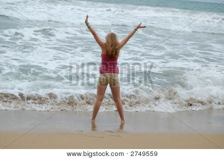 Woman On Beach With Arms Raised