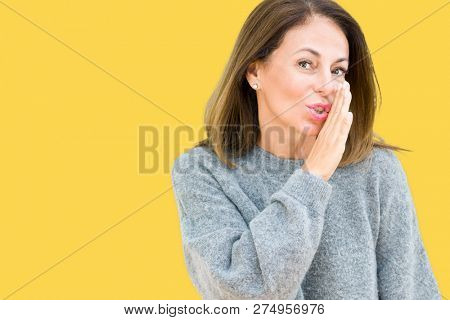 Beautiful middle age woman wearing winter sweater over isolated background hand on mouth telling secret rumor, whispering malicious talk conversation