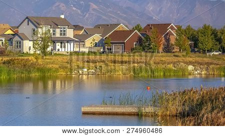 Scenic View With Homes Near Lake Against Mountain