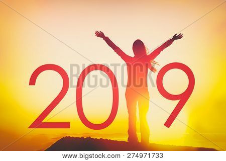 2019 text background for Happy New Year Celebration concept. Woman joyful with open arms in freedom at sunset, silhouette of person winning with resolution goals.