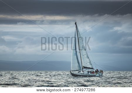 Lone touristic yacht sailing in the sea. Dark cloudy sky before the rain. Northern Ireland. Amazing marine scenery the small ship among the calm water. Ocean scape in grey blue tints.