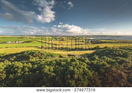 Northern Ireland countryside landscape. The trees, meadows under the blue cloudy sky. Stunning Irish landscape. The farm buildings among the peaceful natural environment. Beauty of wild nature.
