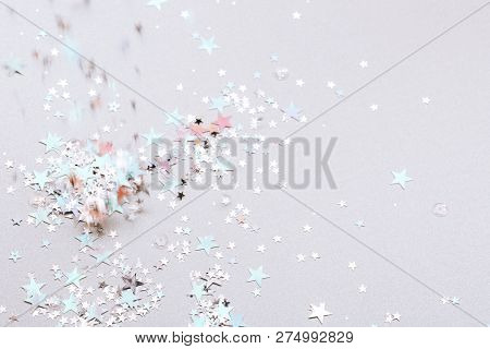 Shot Of Flying Holographic Stars In The Air On Silver Background. Festive Concept. Selective Focus.