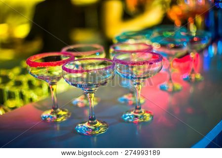 Bocals Hanging On The Bar. Wine Glasses In A Restaurant At A Party. Light Music And Laser Show In A