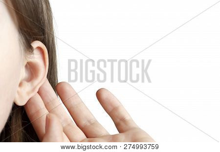 The Girl Listens Attentively With Her Palm To Her Ear, Close-up Isolated On White Background, Indoor