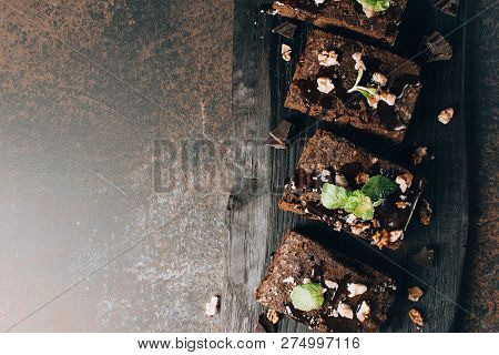 Homemade Dark Chocolate Brownies Topping With Nut Slices And Mint Stacked On Dark Table With Copy Sp