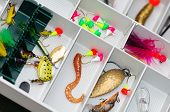 A fisherman tackle box with lures and gear for fishing. poster