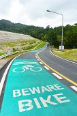 beware bike sign painted on bike lane in dam area and public park poster