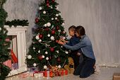 mom with son adorn the Christmas tree lights Christmas new year poster