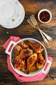 Baked glazed chicken drumsticks. Marinated in teriyaki, apricot jam, wine vinegar and corn starch sauce. White saucepan and plates on  wooden rustic table, top view poster