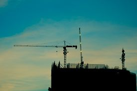 Crane And Building Construction Site At Sunrise. High-quality Stock Photo Image Silhouette Of Constr