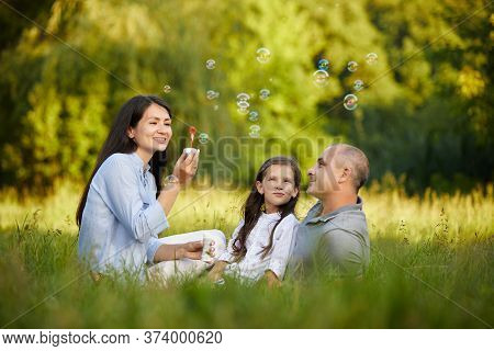 Happy Family With Child Girl Blow Soap Bubbles Outside