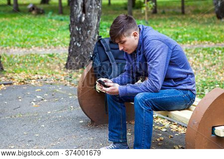 Pensive Young Man With A Phone Sit On The Bench In The Autumn Park
