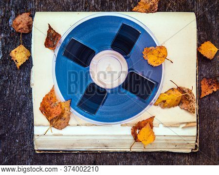 Vintage Reel With A Tape And Autumnal Leaves On The Old Book Closeup