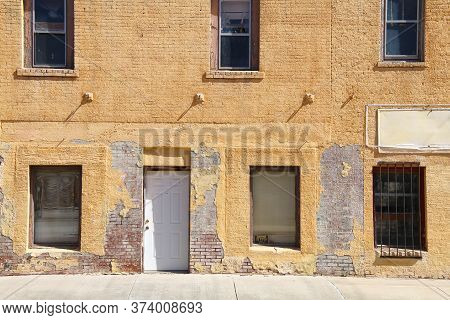 An Abandoned Empty Business Shop Building Front With Vintage Yellow Brick Wall