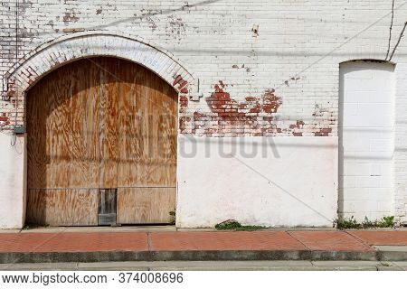 An Abandoned Warehouse Building With Boarded Up Loading Dock Bay Door With White Painted Brick