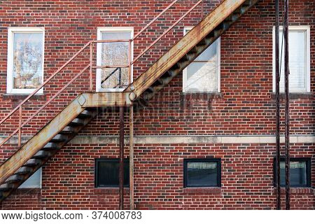 Set Of Back Alley Rusted Fire Escape Stairs In Front Of White Windows On A Red Brick Building
