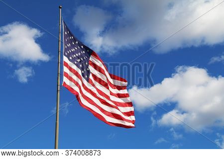 A Bright Flowing Waving American Flag On A Sunny Day With A Few White Clouds