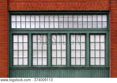 A Bright Set Of Green Shop Windows And A Red Brick Warehouse Wall