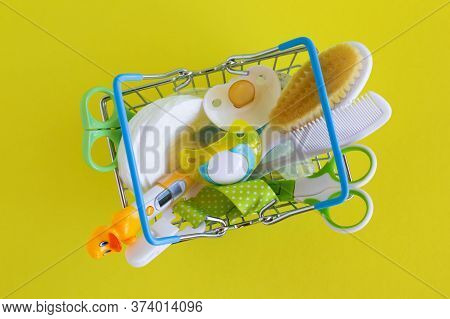 Flat Lay On Shopping Basket With Baby Care Items - Scissors, Hairbrushes, Pacifiers, Thermometer, Co