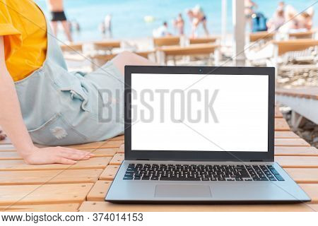 A Person Is Lying On A Sunbed, And Next To It Is A Laptop. In The Background, The Sea And The Beach.