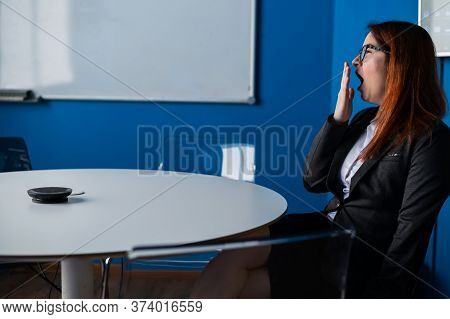 Tired Red-haired Business Woman In Glasses And A Suit Bored In An Empty Conference Room. An Office C