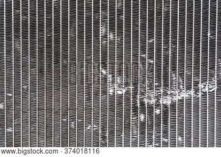 Close Up The Damage Of Car Cooling Radiator. The Old Radiator Of The Damaged Car.