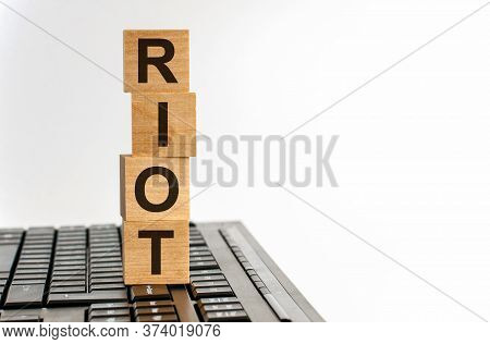 Concept Image A Wooden Block And Word - Riot - On White Background. The Cubes Are Located On The Key