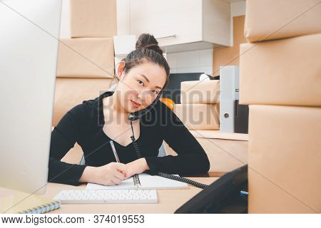 Asian Beautiful Woman Receiving Order By Phone And Notebooks In Selling Products Online, Working At