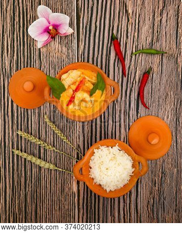 Chicken Panang Curry with Rice is Thai food sauce curry and basil leaf and coconut milk put on Terracotta pot on a banana leaf in wooden background
