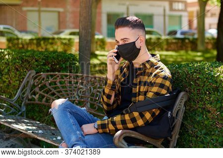 Guy With A Mask Is Sitting On A Bench While He Calls With His Mobile. Lifestyle, Coronavirus