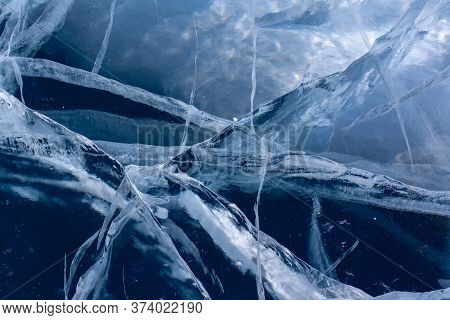 Natural Cracks In The Ice. Cracked Blue Ice On Lake Baikal. Long And Deep Cracks. Horizontal.