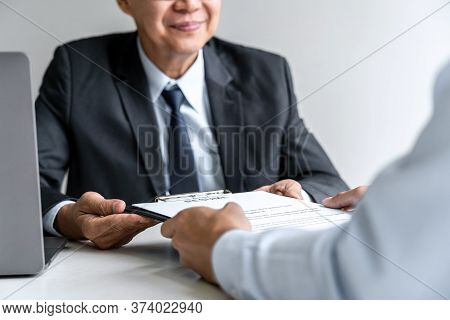 Senior Committee Manager Reading A Resume During A Job Interview, Employer Interviewing To Ask Young