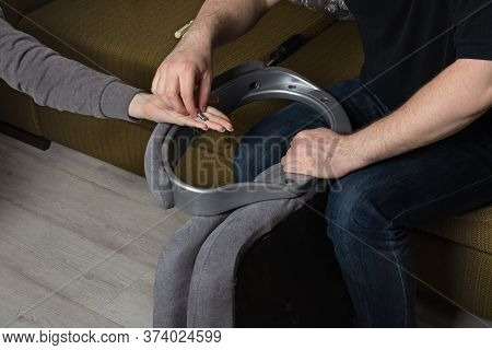 Teamwork In Assembling Chair.man Assembling  Office Chair Indoors.  Girl Helps A Man Repair  Chair A