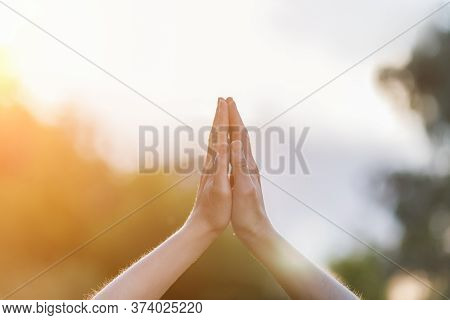 The Concept Of Prayer.hands Folded For Prayer On A Blurred Background.