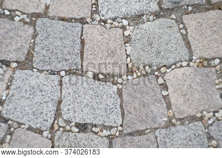 Stone Pavement Texture. Granite Cobblestoned Pavement Background. Abstract Background Of Old Cobbles