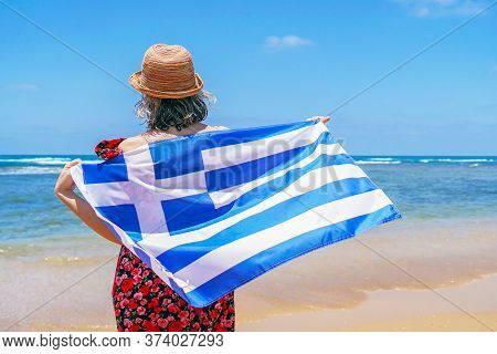 Woman In Hat With Greece Flag At The Beach. Girl Holds An Greece Flag While Standing On The Beach, B