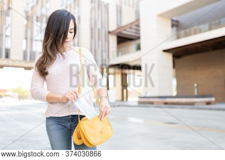 Caucasian Mid Adult Woman Removing Face Mask From Purse During Coronavirus Outbreak